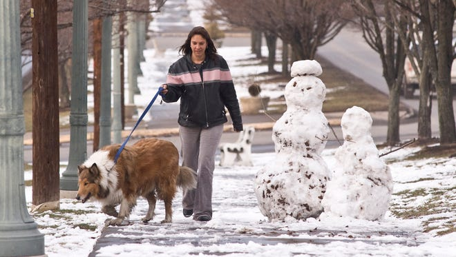 Brenda Snyder, of Shamokin, Pa., walks her dog, Cliff, around two snowmen on a park plot along Market Street in Shamokin on Jan. 23, 2015.