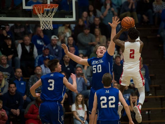 Bosse's Mekhi Lairy (2) takes a jump shot over Memorial's Drew Hart (50) during the Class 3A Boonville Sectional final at Boonville High School on Saturday, March 3, 2018. Bosse defeated Memorial 67-62.