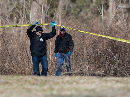 Bartholomew County coroner Clayton Nolting, left, walks under police tape after the body of Jacqueline Watts was discovered in Columbus, Ind., Saturday, March 4, 2017. The Columbus Police Department say officers found Jacqueline Watts' body Saturday morning on a sandbar by the Flatrock River in the city's Noblitt Park.