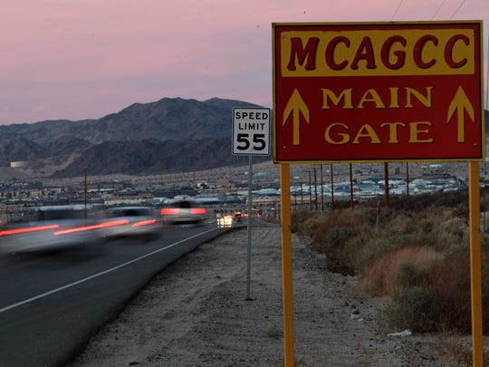 Friday evening traffic travels along Adobe Road to and from the Marine Corps Air Ground Combat Center in Twentynine Palms, which is seen in the distance on Feb. 7, 2014.