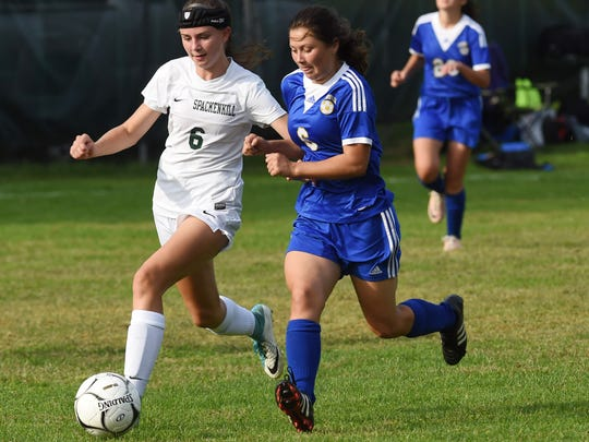 Spackenkill's Kaitlyn Kilpert, left, takes the ball down the field while Ellenville's Sophie Santiago, right, defends during Tuesday's game.