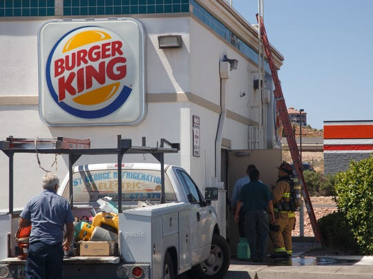 A Washington City Fire Department firefighter leads Burger King employees back into the building after ensuring that the fire that started in the air conditioning unit on the roof of the Burger King in Washington was completely extinguished Monday, July 27, 2015.