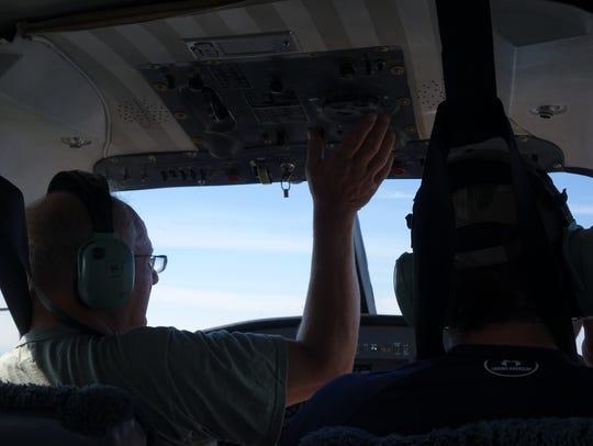 Pilot Louie Kuhn adjusts the trim on an Aero Commander