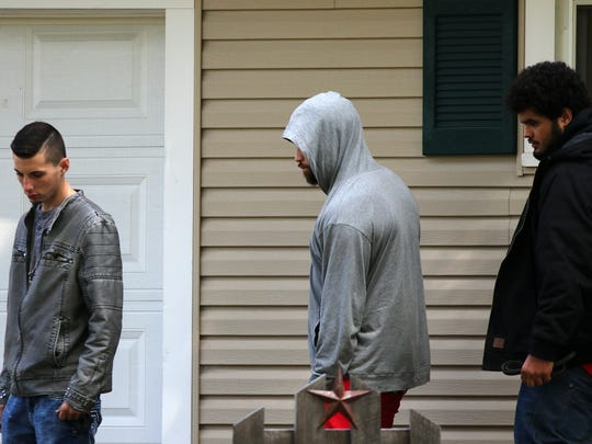 People leave the residence on Illinois Avenue after talking with the homeowner where a crash took place Sunday morning.