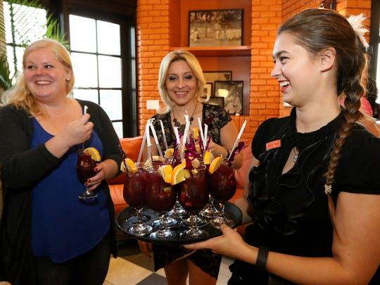 Employee, Carolyne Kelly, serves sangria during the grand opening of Havana Central located at the Menlo Park Mall, Edison, NJ, November 4, 2015.  Mary Iuvone/For the Courier News