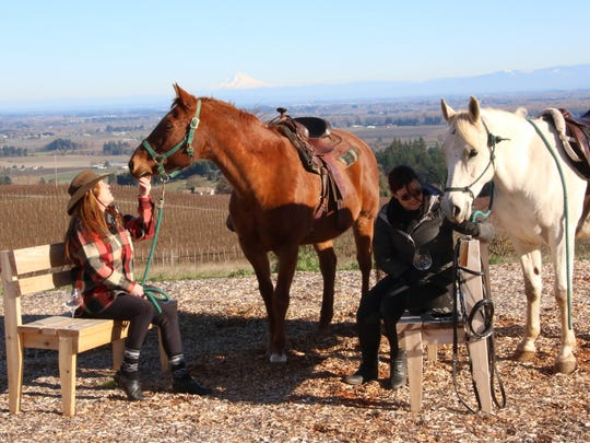 Cathy Eshleman and Dani Gregoire sit with their horses while enjoying wine at Brooks Wines in Amity on Friday, Nov. 27, 2015.