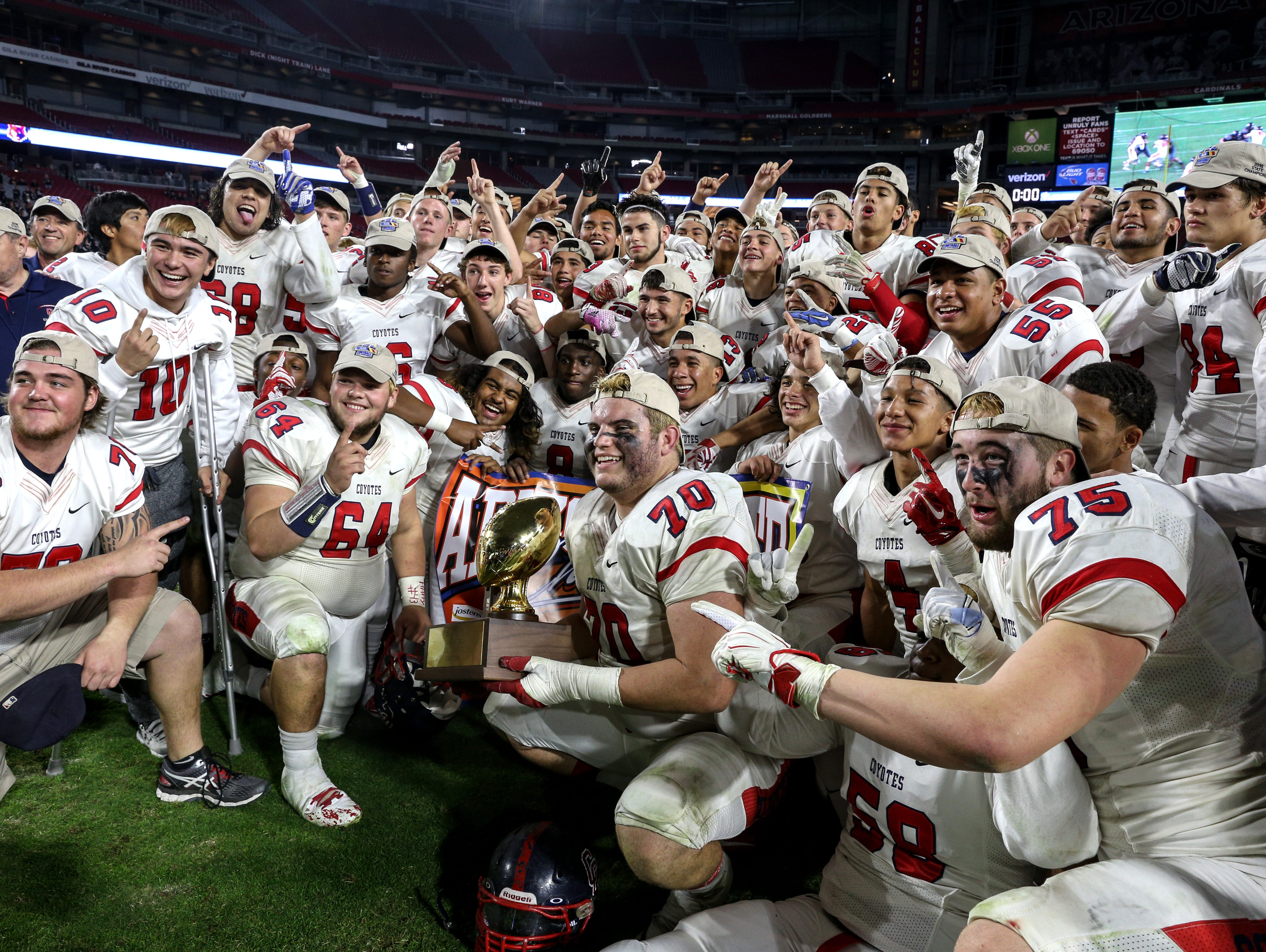 The Peoria Centennial football team celebrates after defeating Mesa Desert Ridge for the Division I state championship at University of Phoenix Stadium in Glendale.