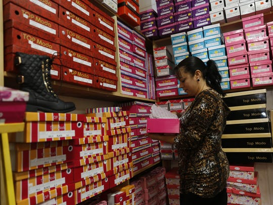 Store manager Alma Hernandez sets up a display of shoes Thursday at Sahemi Shoes and More in Farmington.