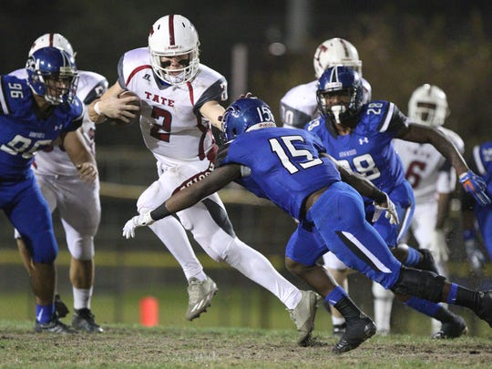 SEFFNER, FL. 12/4/2015 -- Tate Aggies quarterback Sawyer Smith scarambles for yardage by stiff-arming Armwood safety Tyler Scott in Friday's Class 6A state semigfinal at Lyle Flagg Field. The Aggies fell to the Hawks 53-19.