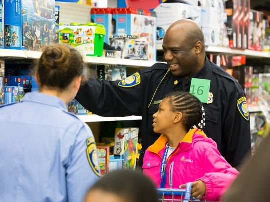 Battle Creek Police Major Austin Simons helps Kiyah Collins pick out Legos  during the Shop With a Cop event at Wal-Mart on Saturday morning.