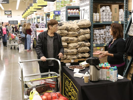 A customer samples products from a vendor at Cash & Carry's grand opening in South Salem on Wednesday, Dec. 9, 2015.
