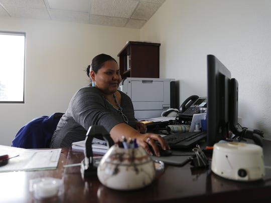 Program supervisor Erica C. Lee works at her desk Dec. 10 at the Navajo Nation Department for Self Reliance in Farmington.