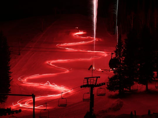 The snow reflects an orange glow during Ski Apache's Torchlight parade.