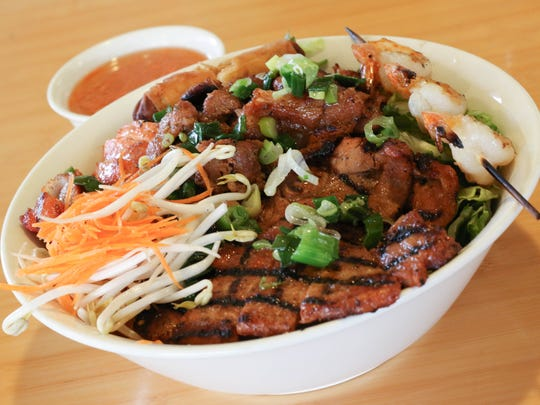 Rice vermicelli with grilled pork slices, pork chop, shrimp and chicken plus a crispy egg roll is served at Super Pho  on Lancaster Drive NE.