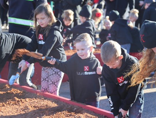 """Children dig in the dirt of a large boxed """"X"""" during"""