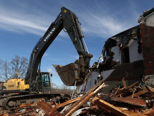 An excavator picks up debris during a demolition of