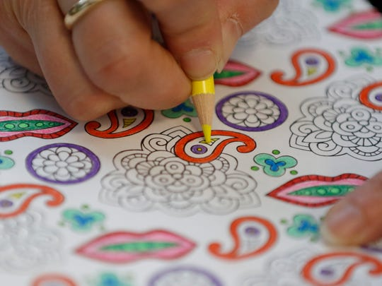 Amy Eisenschink carefully chooses her colors for her coloring page at the Manitowoc Public Library adult coloring club on March 4.