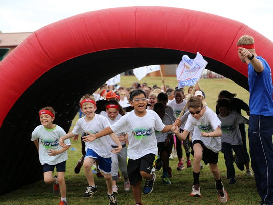 Students from Bethel Elementary School rush onto the Boosterthon track to participate in the Color Run.