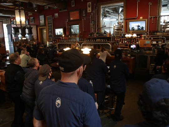 Deschutes employees at the Portland brewpub watch the live webcast on Tuesday of the announcement of the company's new brewery in Roanoke, Virginia.