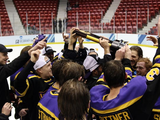 Members of the University of Wisconsin-Stevens Point men's hockey team celebrate with the championship trophy after defeating St. Norbert 5-1 in the Division III national title game in Lake Placid, N.Y. on March 26.