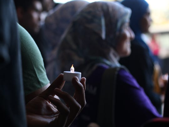 A student holds a candle in a crowd of people congregated
