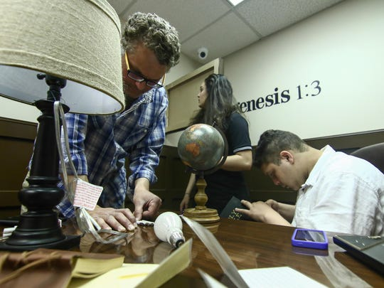 Adam Sharkawy, with his kids Jenna, 15, and Zane, 16, try to solve puzzles and riddles to escape the Shawshank room at Axxiom Escape Rooms in Brandywine Hundred on Friday.
