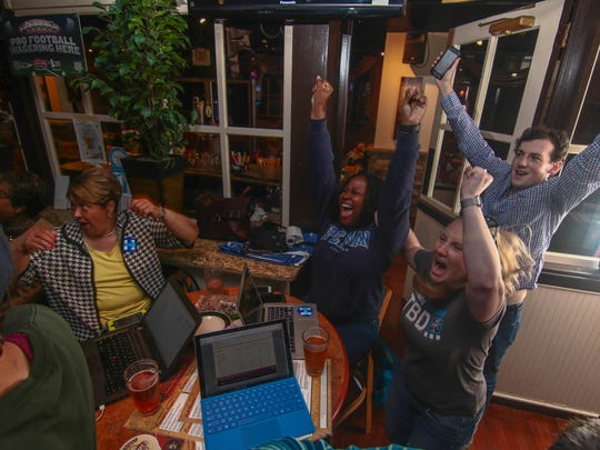 State Sen. Margaret Rose Henry, (from left) Cimone Philpotts, Benjamin Mercel-Golden and Courtney McGregor react to news that Hillary Clinton won the Delaware primary during a victory party at Timothy's Riverfront Grille in Wilmington on Tuesday. Donald Trump secured the state GOP nomination.