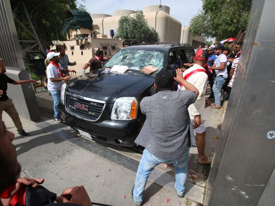 Iraqi protesters throw stones at a vehicle they believe