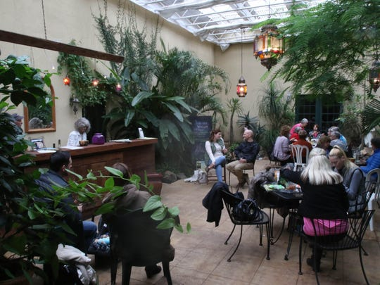 Guests enjoy wine in the tasting room at Villa Catalana Cellars, set in a gardenlike setting in a courtyard that has been converted into a lush space for wine tasting.