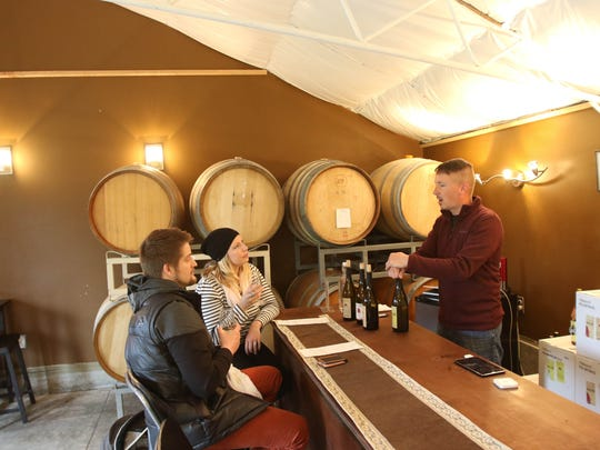 Hanson Vineyards owner and winemaker Jason Hanson, right, discusses his wine with Paul Hoover and his wife, Tayler Anderson, who were visiting his winery in Woodburn from Portland.