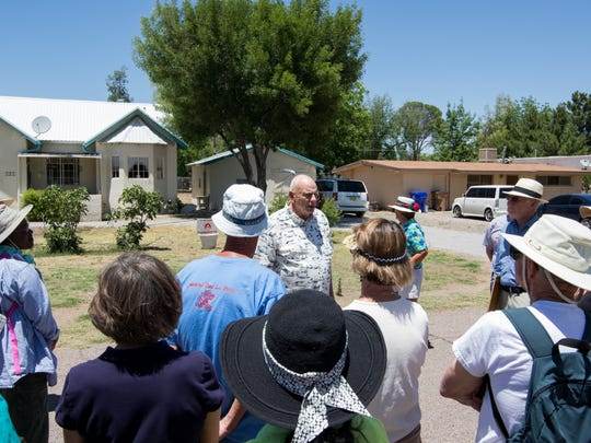 Lester Heinzman tells the story of his historic home to the Mesilla Park history walking tour group as it paused by his house.