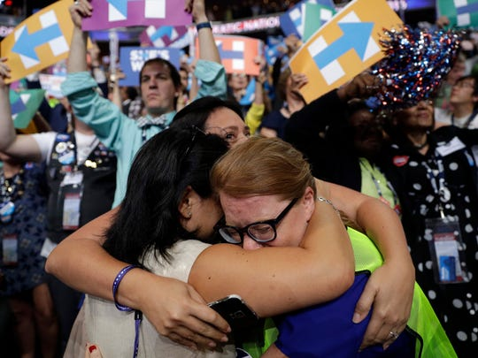 Carrie Pugh, left, Katrina Mendiola and Mayors Wegmann cry as Hillary Clinton officially becomes the first woman to be the presidential nominee of a major U.S. political party during the second day session of the Democratic National Convention in Philadelphia Tuesday.