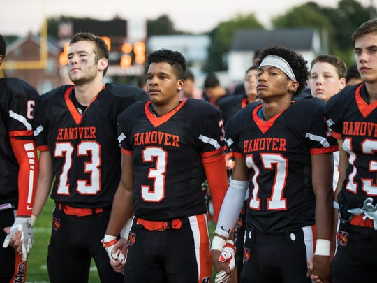 Hanover football players hold hands during the national anthem before the Nighthawks' game on Sept. 23. Theo Johnson (17) opted not to protest during the anthem after talking to coaches and teammates.