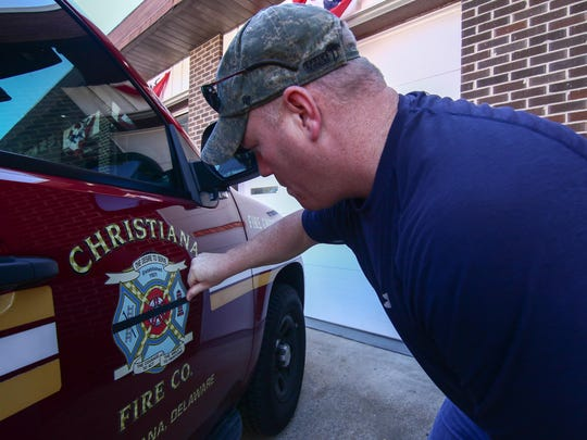 Fire Chief Richard J. Perillo places a black stripe on Christiana Fire Company's logo in honor of fallen firefighters Jerry Fickes and Lt. Christopher Leach on Sunday, Sept. 25, 2016, at Christiana Fire Company in Christiana.