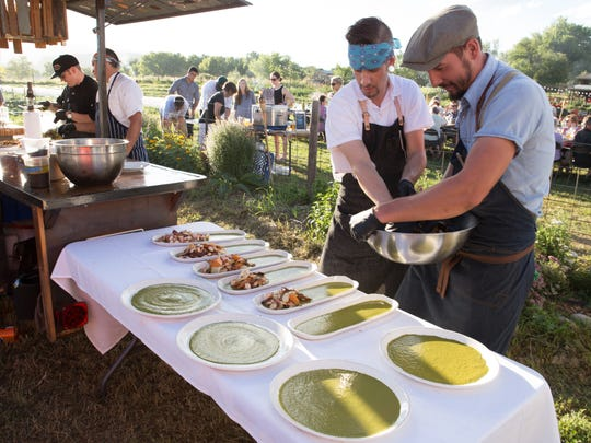 Trevor Burt of Jax Fish House and Brandon Spain of The Tramp About food truck prepare plates of seared octopus salad at Spring Kite Farm.