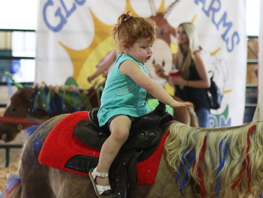 Tyler Henley Fowler, 2, rides on a pony during a pony