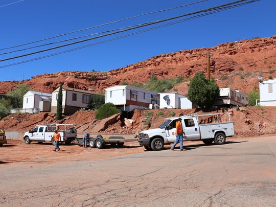 City workers dig out mud that fell from the red hillside