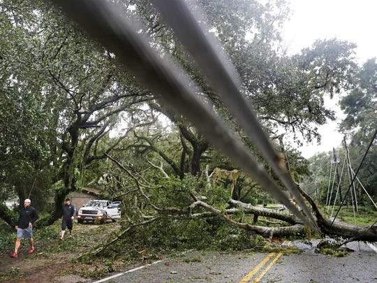 A tree and power lines blown over by Hurricane Matthew lay across a road on St. Simons Island, Ga., Saturday, Oct. 8, 2016. Matthew plowed north along the Atlantic coast, flooding towns and gouging out roads in its path. (AP Photo/David Goldman)