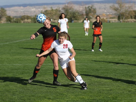Aztec's Autumn Petersen, left, beats Albuquerque Academy's Audrey Colter to the ball on Thursday at the Bernalillo Soccer Complex.