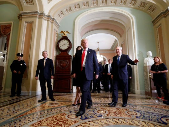 Donald Trump and his wife, Melania, walk with Senate Majority Leader Mitch McConnell on Capitol Hill following a meeting Thursday.
