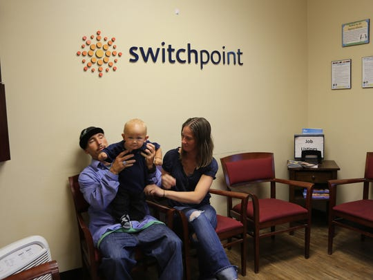 A family at SwitchPoint plays with their 1-year-old son at the shelter.