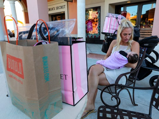 """Adeline Anderson, 7 weeks old, hangs with her aunt, Monica MacDonald of Wilmar, MN, as they shop with family members at Coconut Point Mall. """"We are taking turns shopping and passing off the baby,"""" Monica said."""