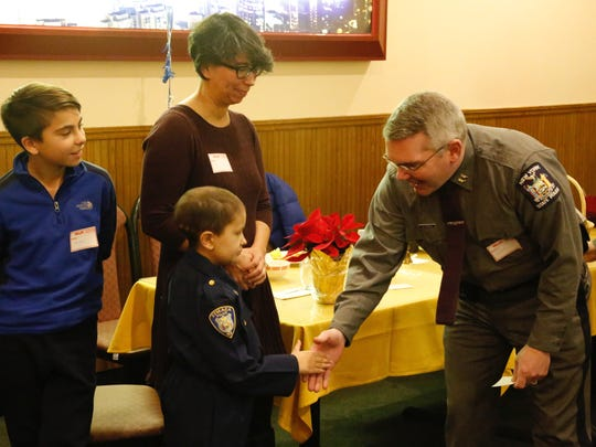 Colin Toland shook the hands of many police officers and residents at a Kiwanis Club luncheon. He is joined by his mother, Tamiko Toland, and his brother, Aidan.