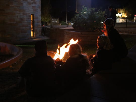 Community members warm up by the fire pit outside Sol
