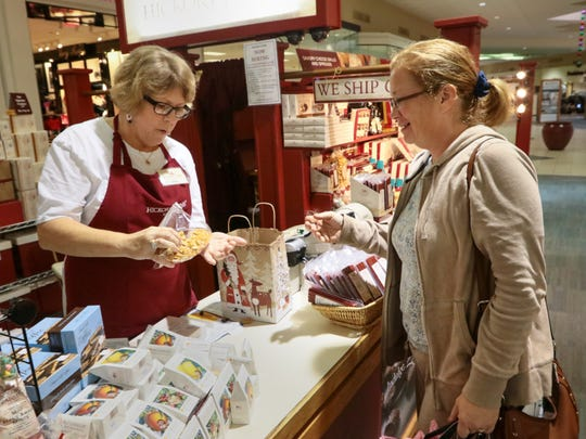 Kacey Morrow, left, a Hickory Farms kiosk manager, sells items from her stand to Cindy Ritchie of Anderson.