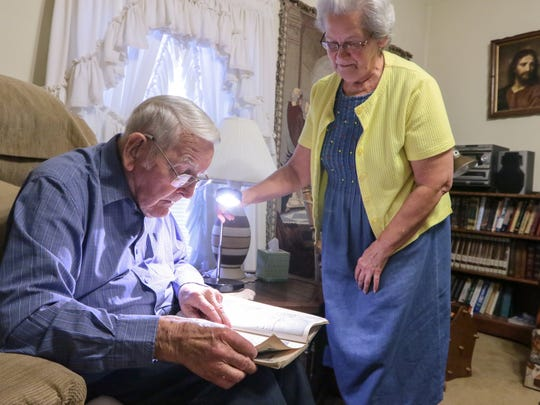 Gerald Cleveland, left, looks at a book of Pearl Harbor attack sketches with his wife Nancy in his living room in Anderson.