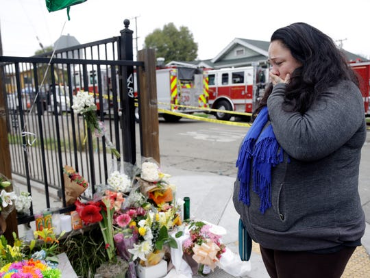 Danielle Boudreaux cries in front of a makeshift memorial