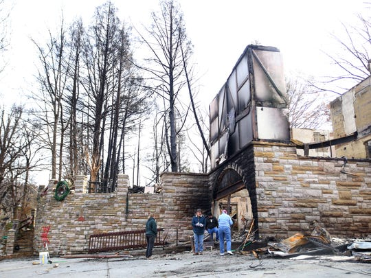 From left LuAnn Bilby, Glen Stocks, Susan Stocks and Broderick Stocks, continue to clean up their bed and breakfast Tudor Inn on West Holly Ridge Rd. in Gatlinburg Thursday, Dec. 8, 2016. The home was destroyed in last week's wildfires.
