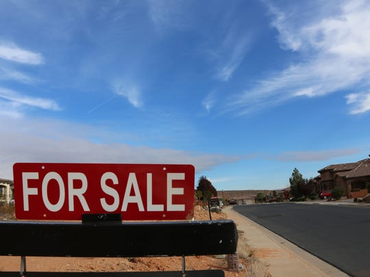 For-sale signs line the roadway along a housing development in the Green Springs area on Friday, Dec. 9, 2016.