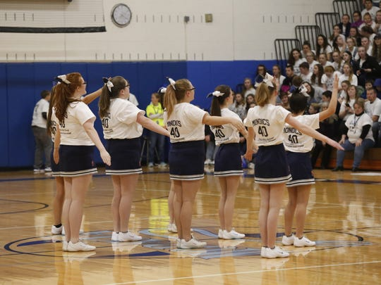 Cheerleaders wear special shirts being sold to raise money for Dustin Mondics, a member of the Moravia basketball team who suffered serious injuries in a car accident on Dec. 27 while heading to basketball practice.